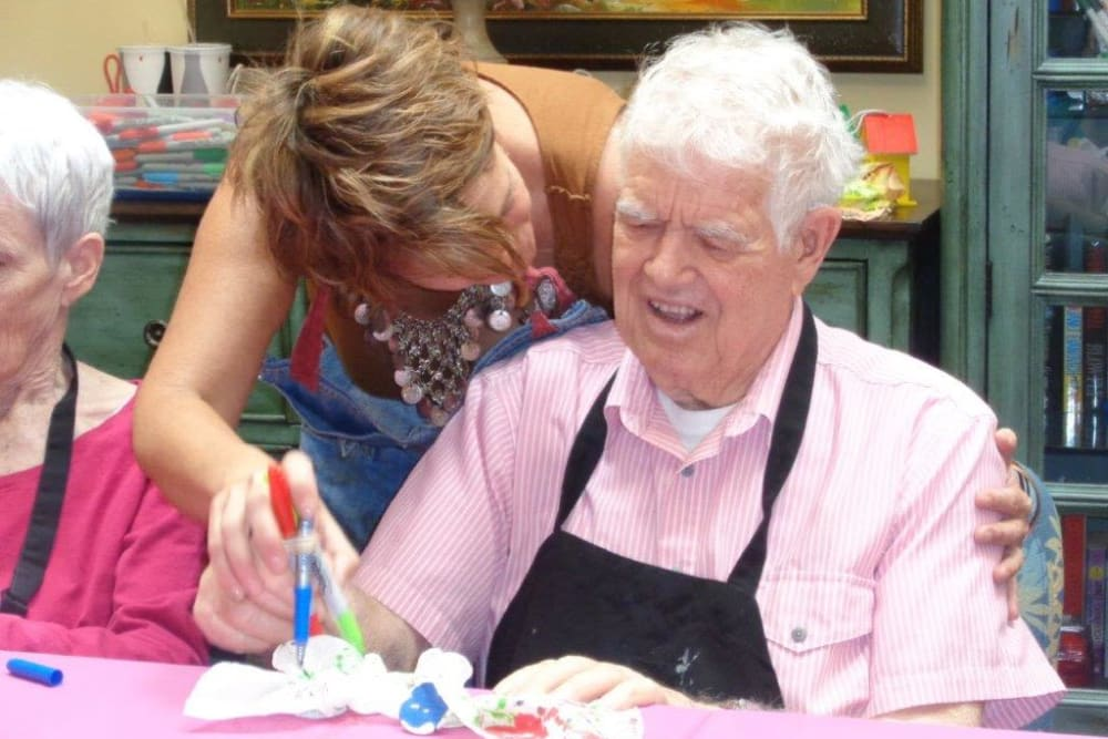 A caretaker assisting a resident with artwork at Avenir Memory Care at Chandler in Chandler, Arizona