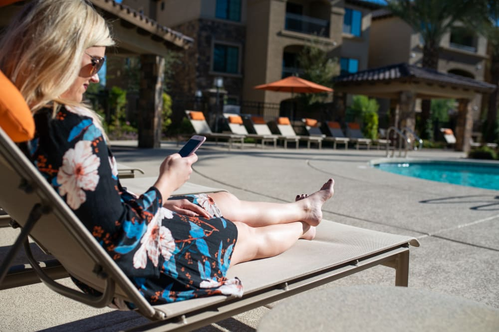 Resident relaxing by the pool at Laguna at Arrowhead Ranch in Glendale, Arizona