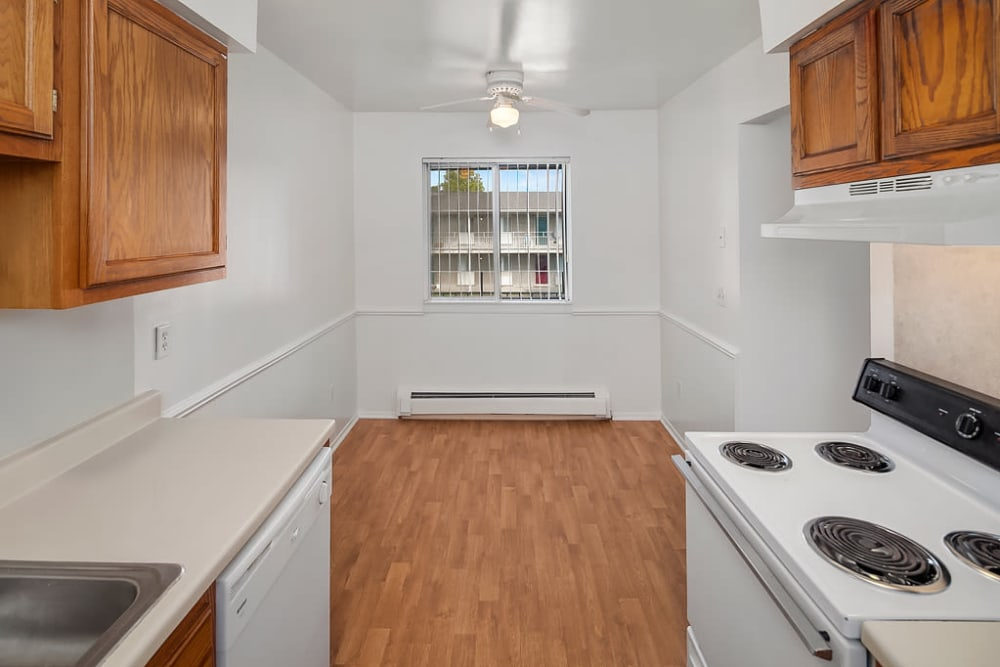 The kitchen leads to the dining room with a window at Concorde Club Apartments in Romulus, Michigan