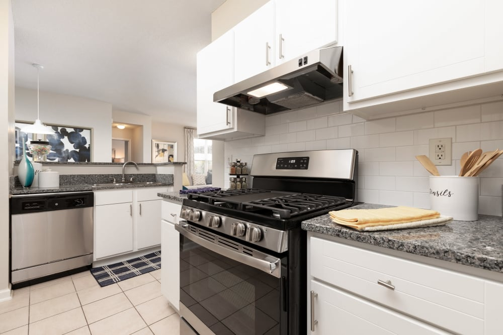 Bright white cabinetry and tiled flooring in a model home's kitchen at 200 East in Durham, North Carolina