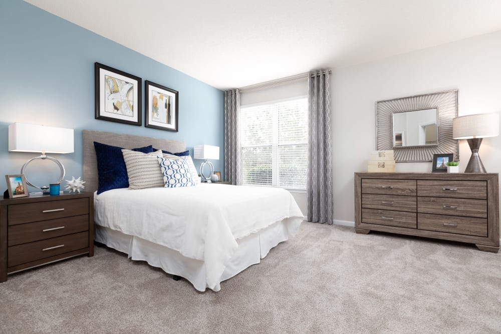 Model apartment's primary bedroom with plush carpeting and floor-to-ceiling windows at 200 East in Durham, North Carolina