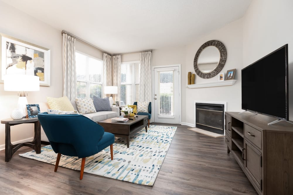 Faux-wood flooring and modern furnishings in a model home's living area at 200 East in Durham, North Carolina