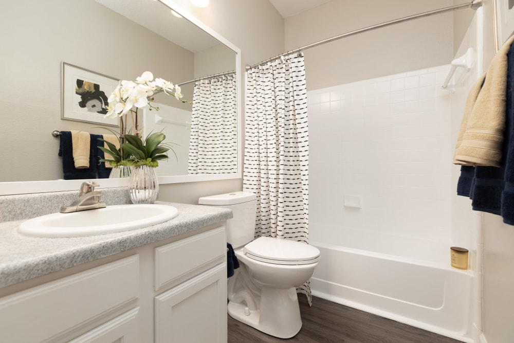 Granite countertop and a large vanity mirror in a model home's bathroom at 200 East in Durham, North Carolina