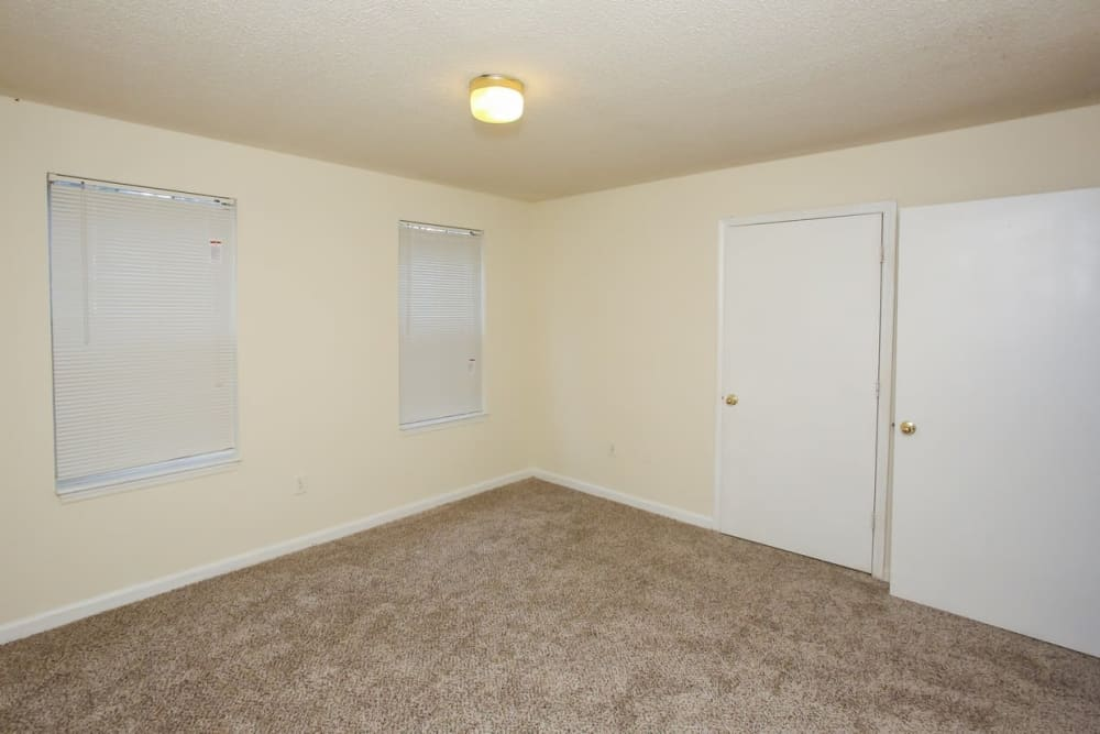 A bedroom with two windows and a closed closet at Oconee Springs Apartments in Gainesville, Georgia