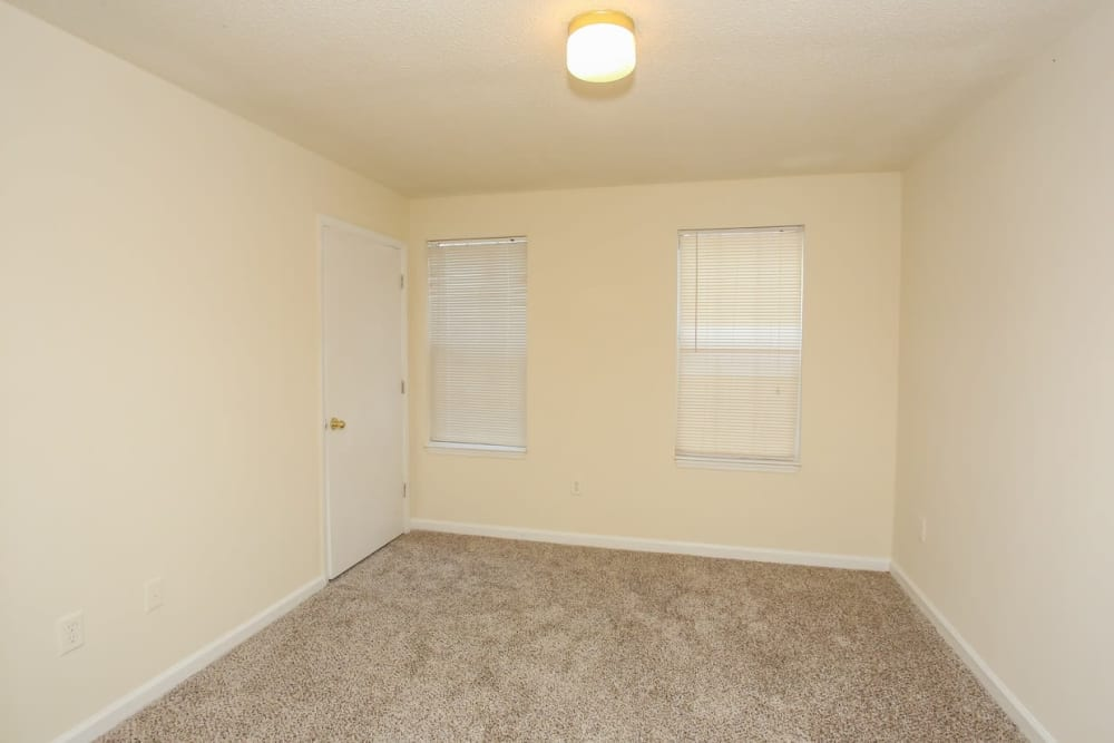 A bedroom with two windows at Oconee Springs Apartments in Gainesville, Georgia