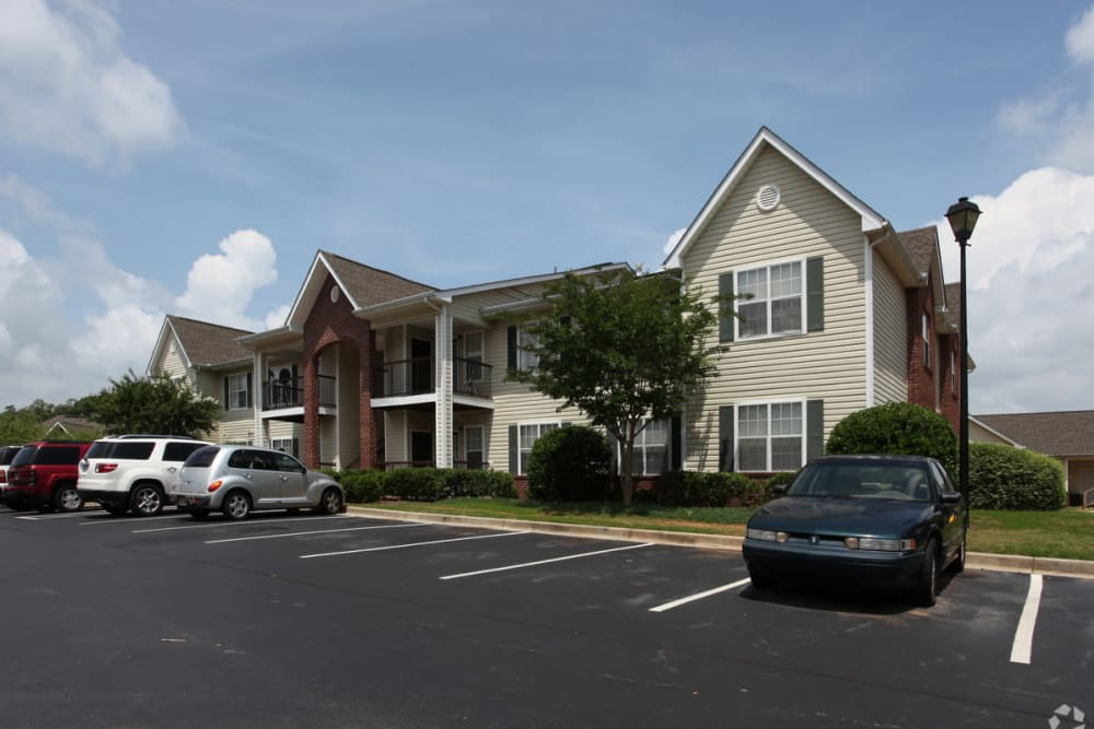 Apartment exterior and resident parking lot at Oconee Springs Apartments in Gainesville, Georgia