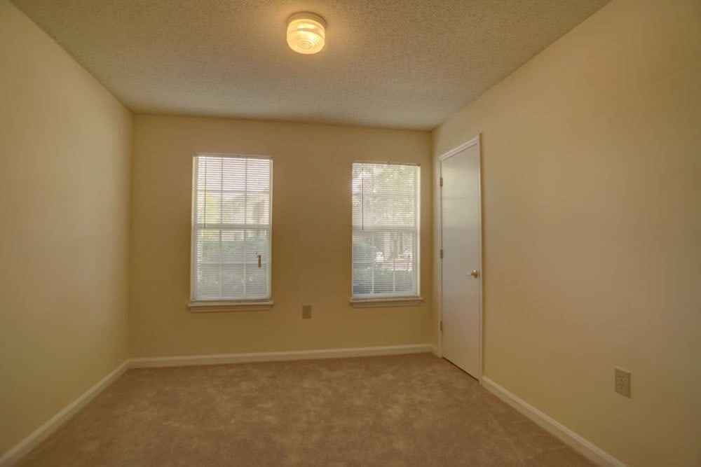 A bedroom with two windows at Etowah Village Apartments in Cartersville, Georgia