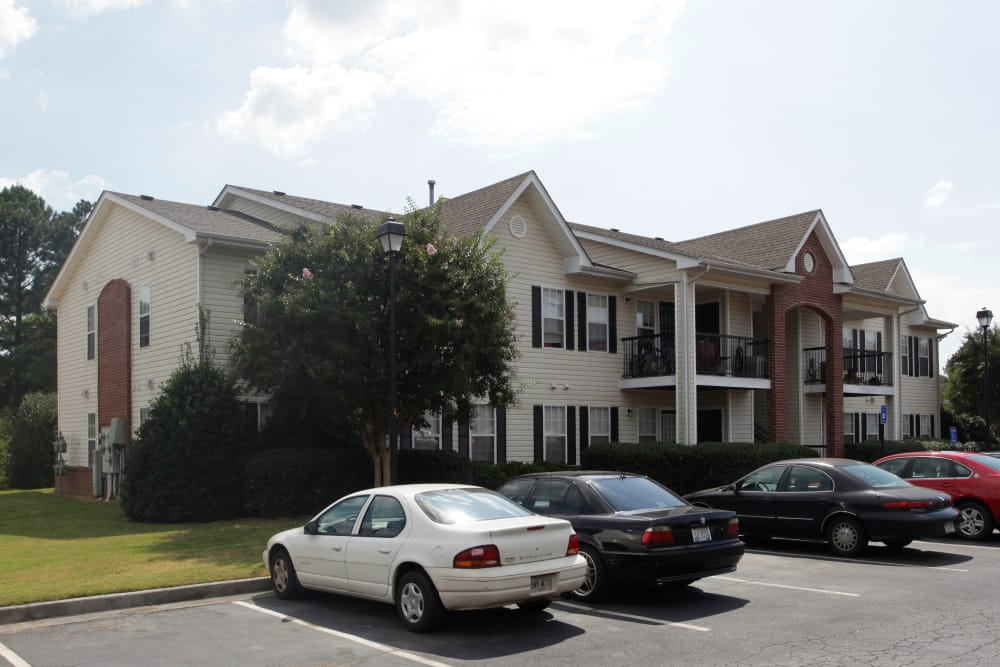 Apartment exterior and resident parking at Etowah Village Apartments in Cartersville, Georgia