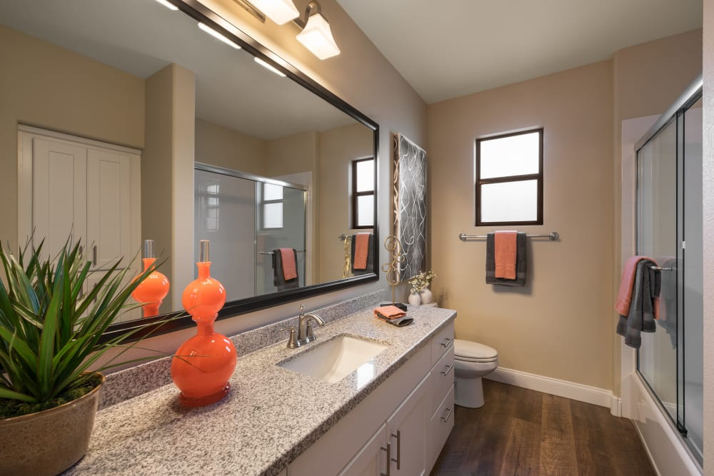 Bathroom with large vanity mirror and granite countertop in model home at San Piedra in Mesa, Arizona