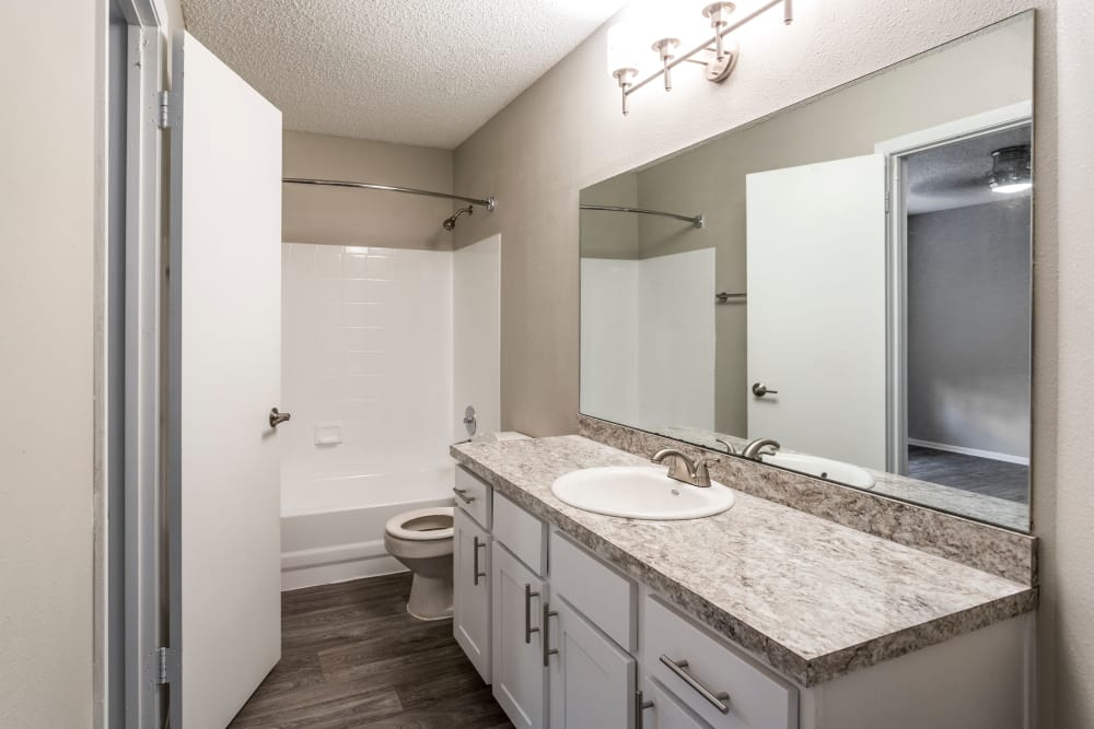 Large vanity mirror in well-lit bathroom of model home at IMT Newport Colony in Casselberry, Florida