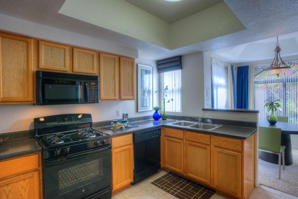 Modern kitchen with sleek black appliances in a model home at San Pedregal in Phoenix, Arizona