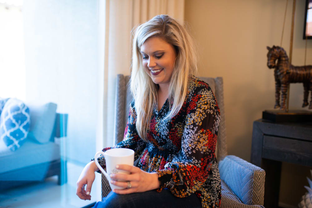 Resident enjoying a cup of coffee in her luxurious apartment at San Lagos in Glendale, Arizona
