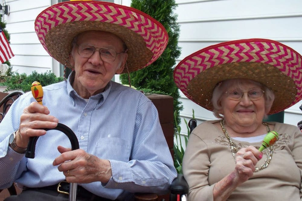 two residents with sombreros and maracas at Heritage Hill Senior Community in Weatherly, Pennsylvania