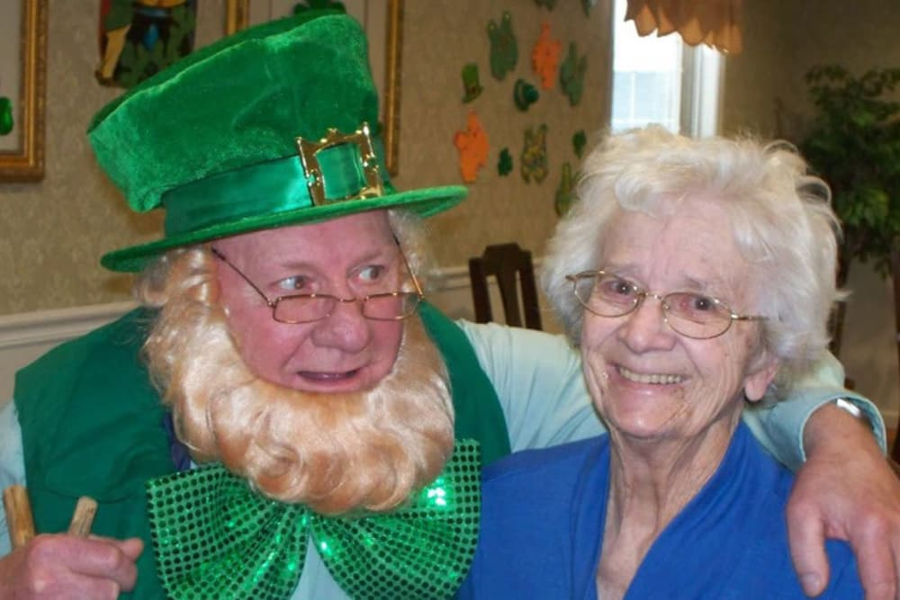 Female resident posing with a man dressed as a leprechaun at Heritage Hill Senior Community in Weatherly, Pennsylvania
