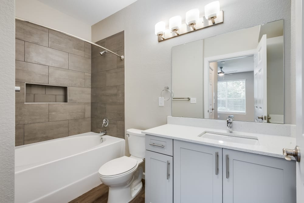 Upgraded bathroom with quartz countertops, tub, and white cabinets