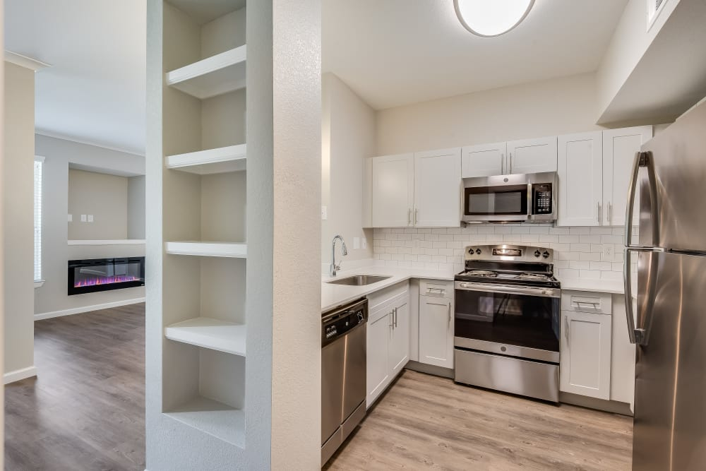 Upgraded apartment interiors with stainless-steel appliances, new subway backsplash, and white quartz countertops