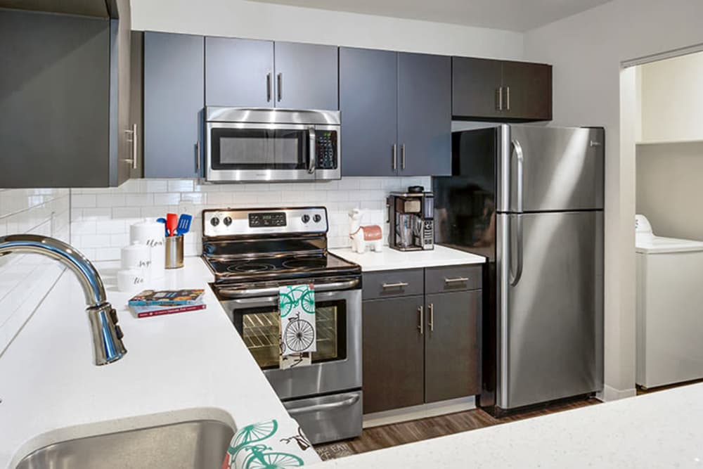 Modern kitchen with stainless-steel appliances at TAVA Waters in Denver, Colorado