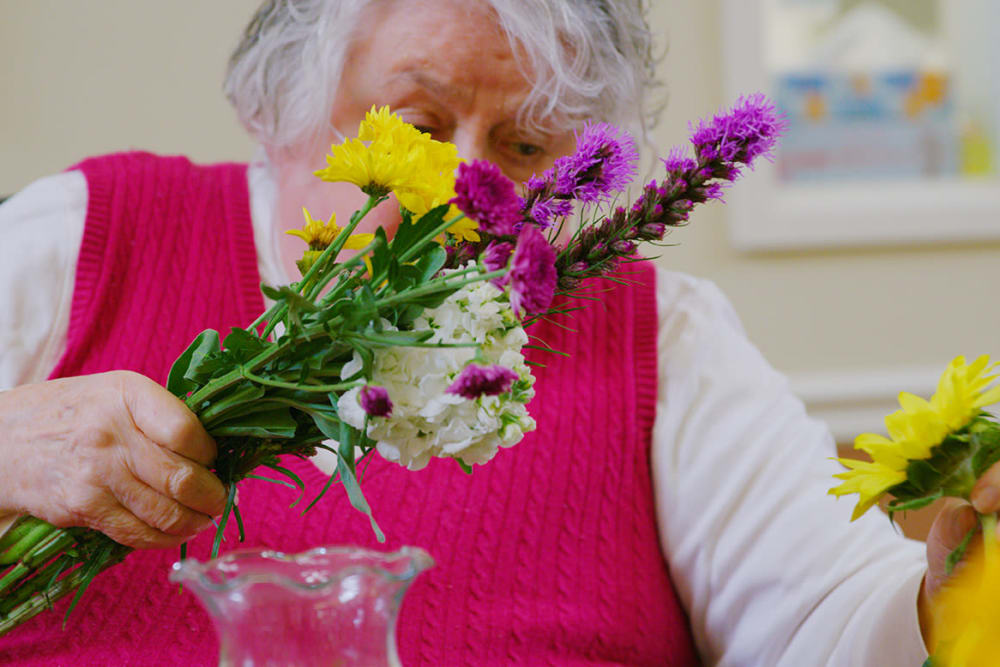 woman creating floral arrangement