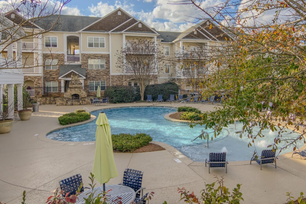 Pool chairs surrounding an outdoor community pool at Apartments at the Venue in Valley, AL