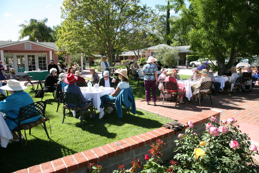 Residents seated at tables in the garden at Gables of Ojai in Ojai, California