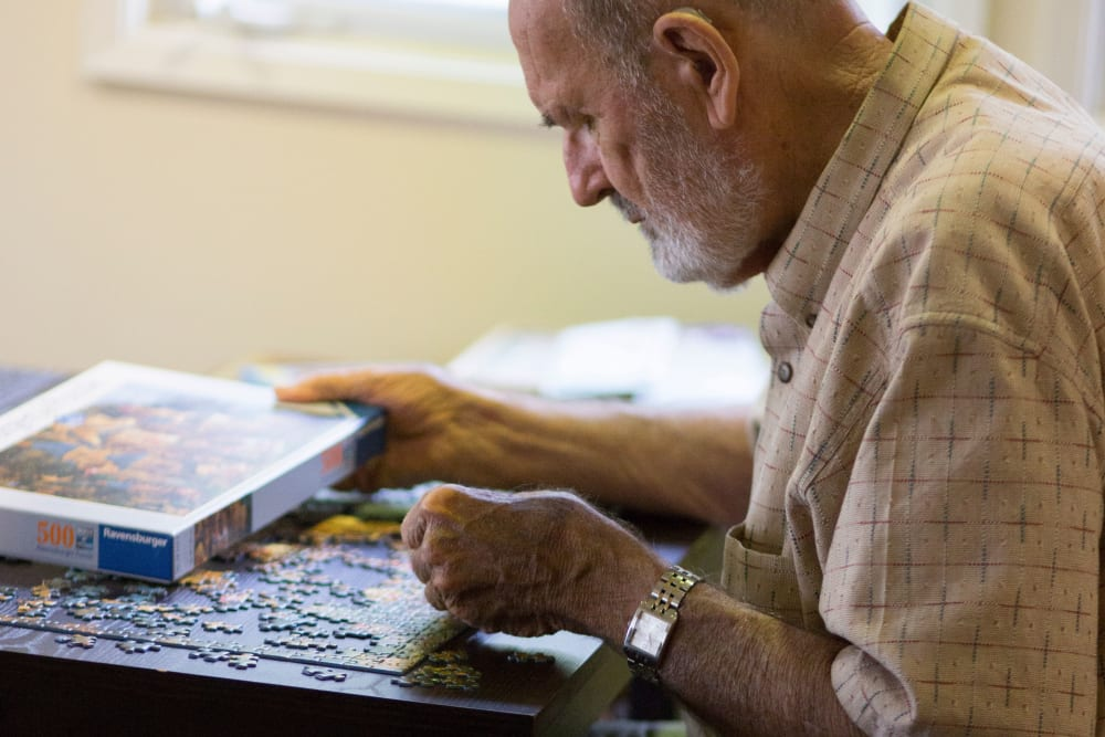 A resident putting together a puzzle at Gables of Ojai in Ojai, California