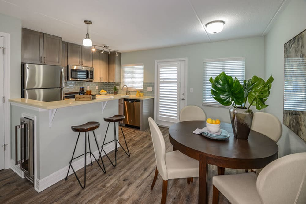 Dining room table and breakfast bar in model home at Sailpointe Apartment Homes in South Pasadena, Florida
