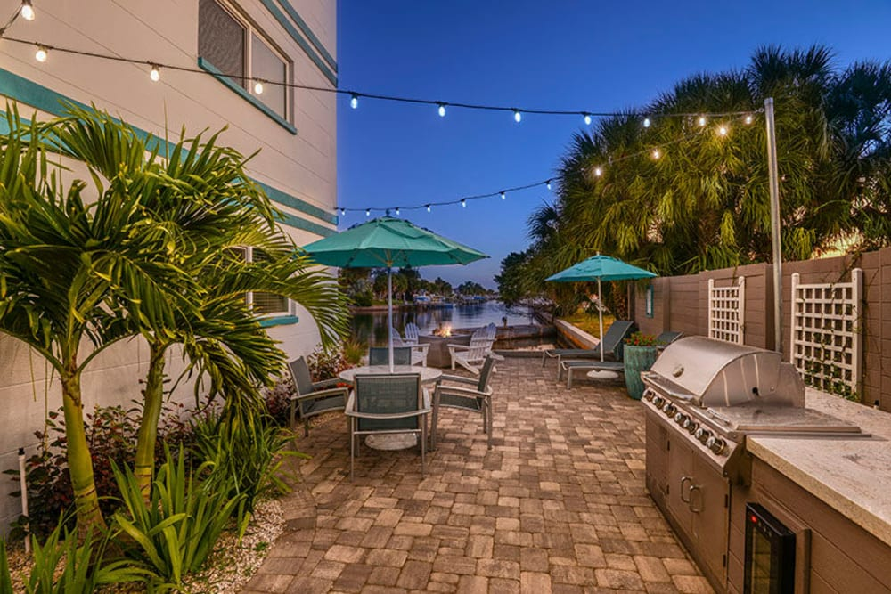 Outdoor patio seating and grill at Sailpointe Apartment Homes in South Pasadena, Florida