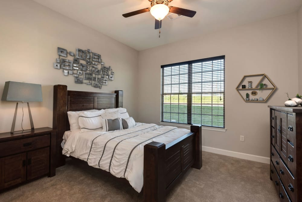 A well decorated bedroom with a ceiling fan at Boulders at Overland Park Apartments in Overland Park, Kansas