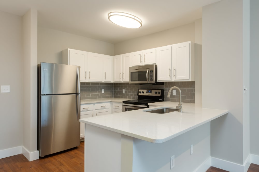 White counter tops and cabinets in kitchen at Kimball Towers at Burlington in Burlington, Massachusetts