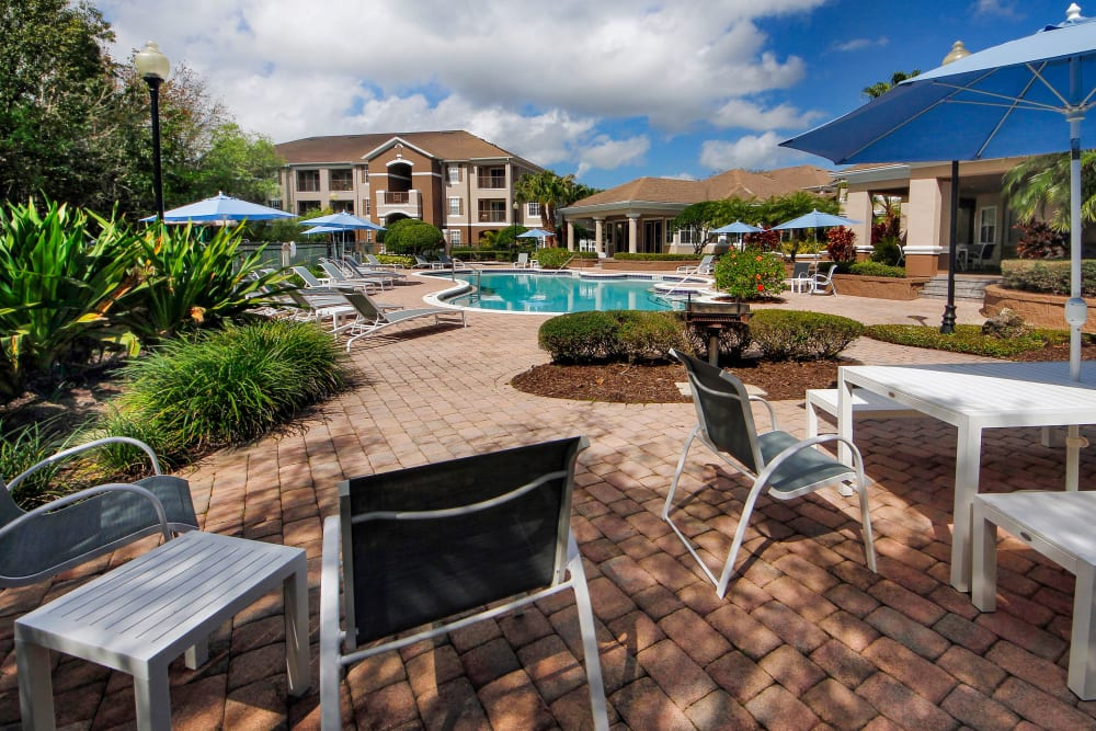 Resort style pool area with covered seating at Legends Winter Springs in Winter Springs, Florida
