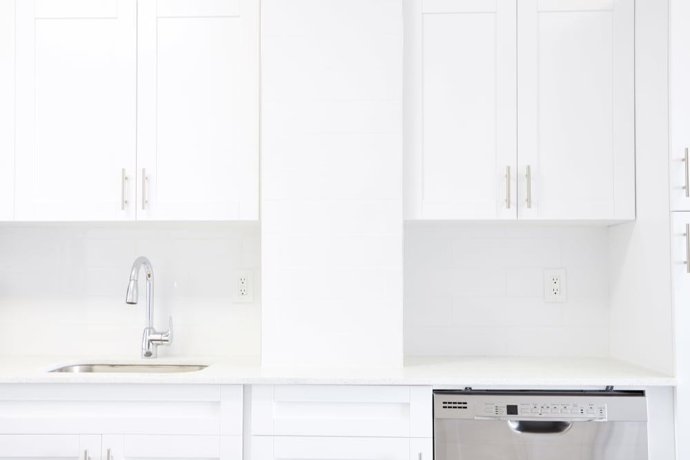 White cabinetry and matching appliances in model home's kitchen at Aliro in North Miami, Florida