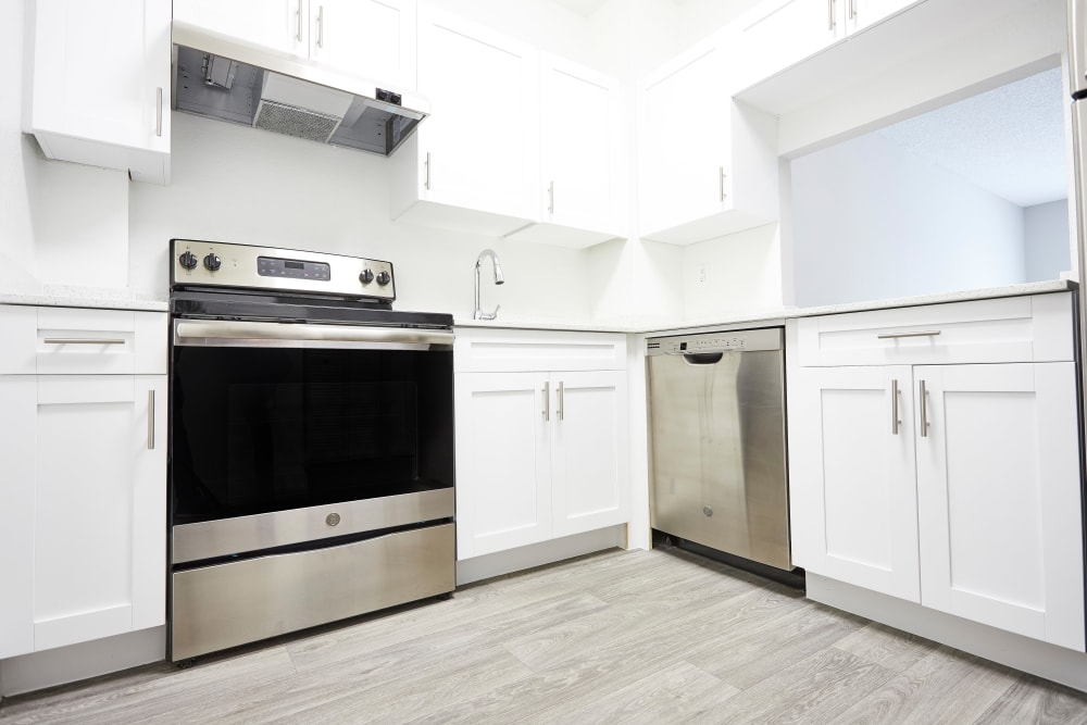 Large, open kitchen with white cabinetry and hardwood floors in model home at Aliro in North Miami, Florida