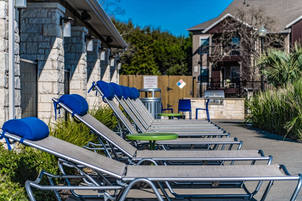 Lounge chairs next to the pool in Austin, Texas at Ethos Apartments