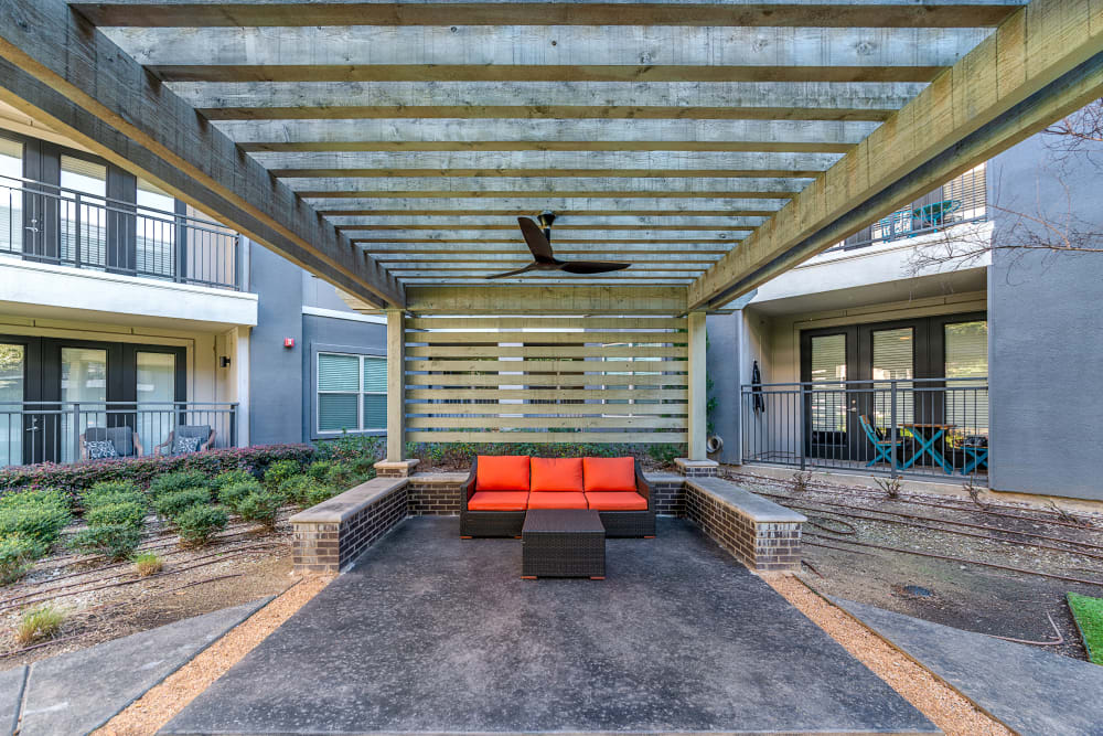 Red lounge chair outside at Axis at Wycliff in Dallas, Texas