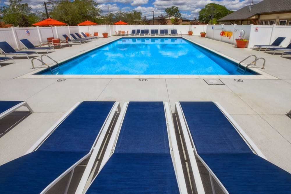 Lounge chairs next to swimming pool at President Madison Apartments in Madison Heights, Michigan