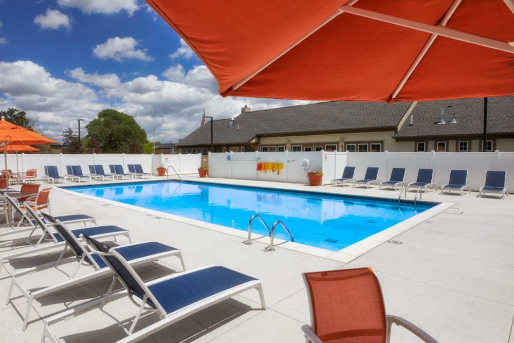 Red umbrella next to pool in Madison Heights, Michigan at President Madison Apartments