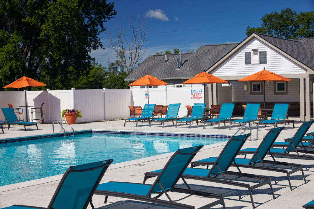 Covered tables on the patio next to the pool in Madison Heights, Michigan at Lexington Village Apartments