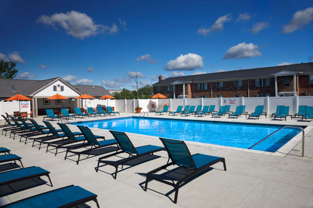 Poolside lounging next to the sparkling pool in Madison Heights, Michigan at Lexington Village Apartments