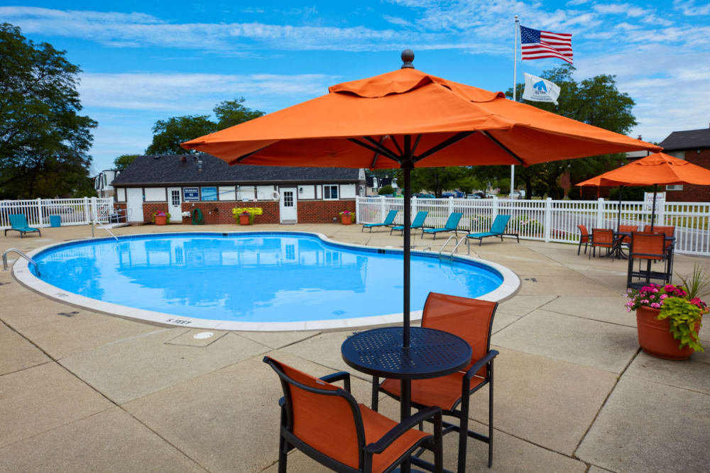 Poolside table and chairs in Sterling Heights, Michigan at Maple Grove Apartments