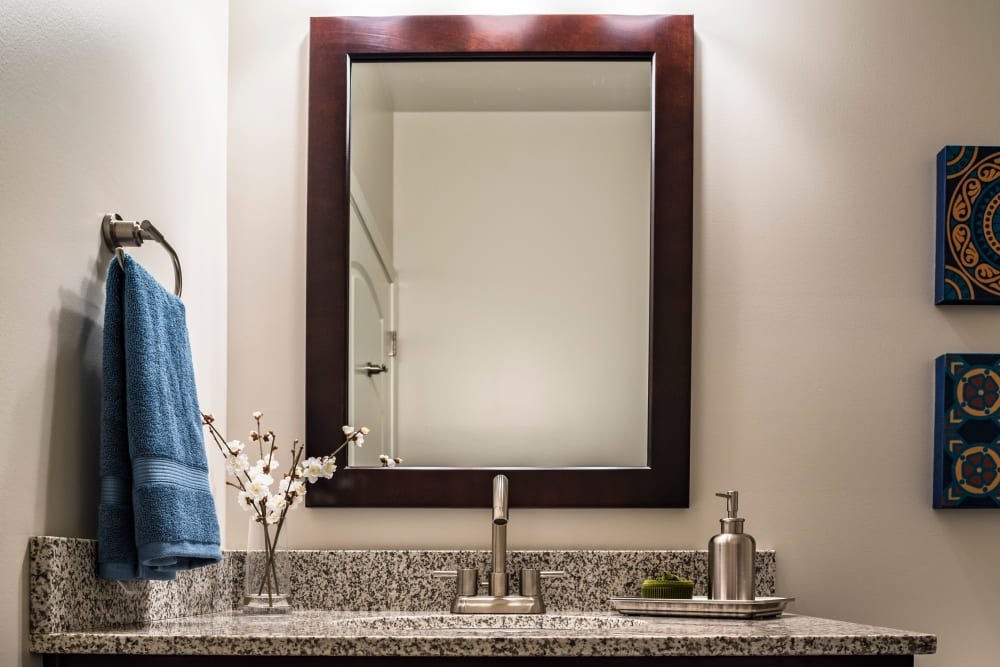 Large vanity mirror and a granite countertop in a model home's bathroom at Valley Farms in Louisville, Kentucky