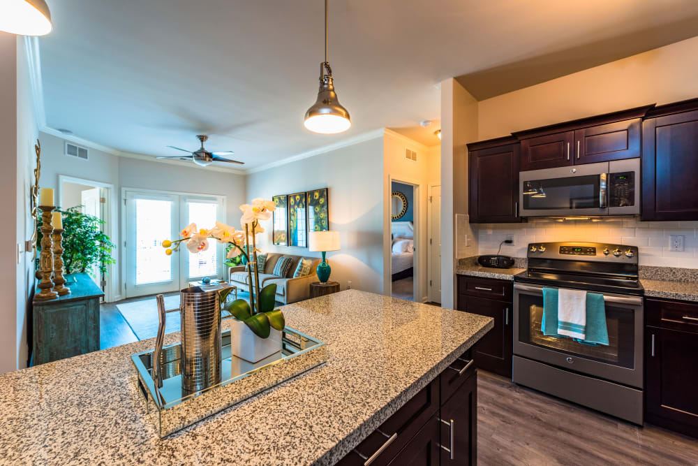 Kitchen island with a granite countertop in a model home's kitchen at Valley Farms in Louisville, Kentucky