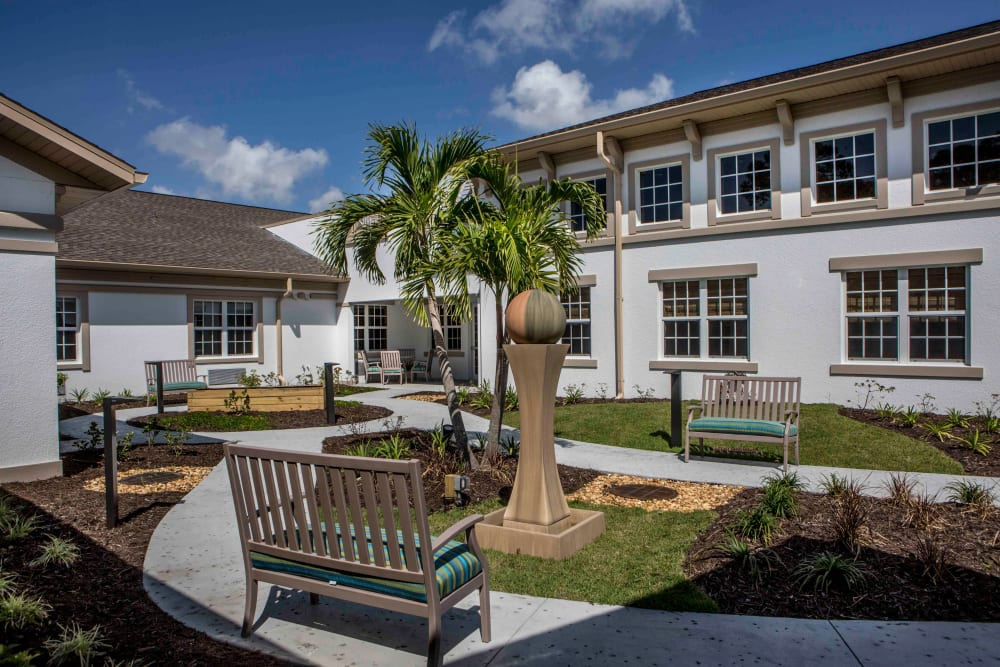 Sunlit outdoor walkway with benches at Beach House Assisted Living & Memory Care Naples in Naples, Florida