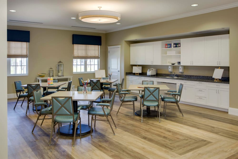 Dining room and community kitchen at Beach House Assisted Living & Memory Care Naples in Naples, Florida