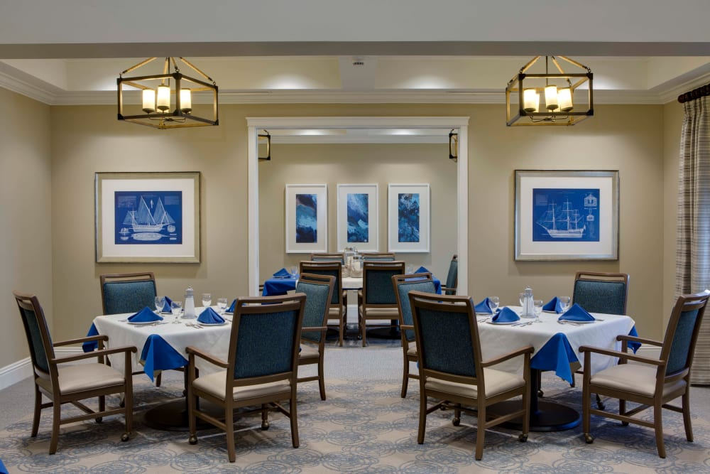 Dining rooms with tables set for four at Beach House Assisted Living & Memory Care Naples in Naples, Florida