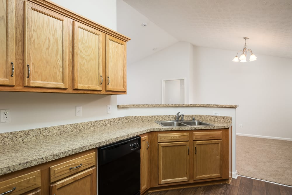 Spacious granite countertop and hardwood floor in an apartment home's kitchen at Valley Farms in Louisville, Kentucky