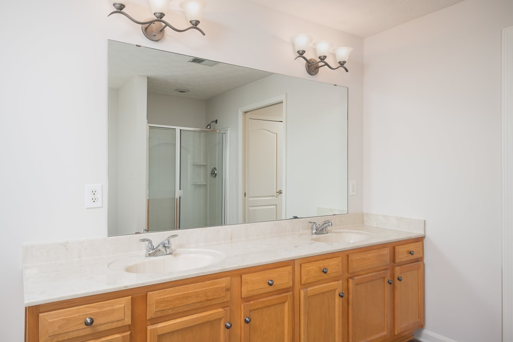 Well-lit bathroom with a large vanity mirror in an apartment home at Valley Farms in Louisville, Kentucky