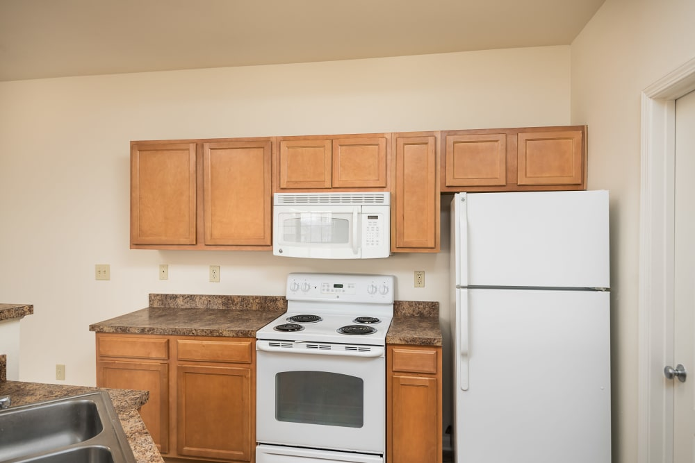 White appliances and granite countertops in an apartment home's kitchen at Valley Farms in Louisville, Kentucky