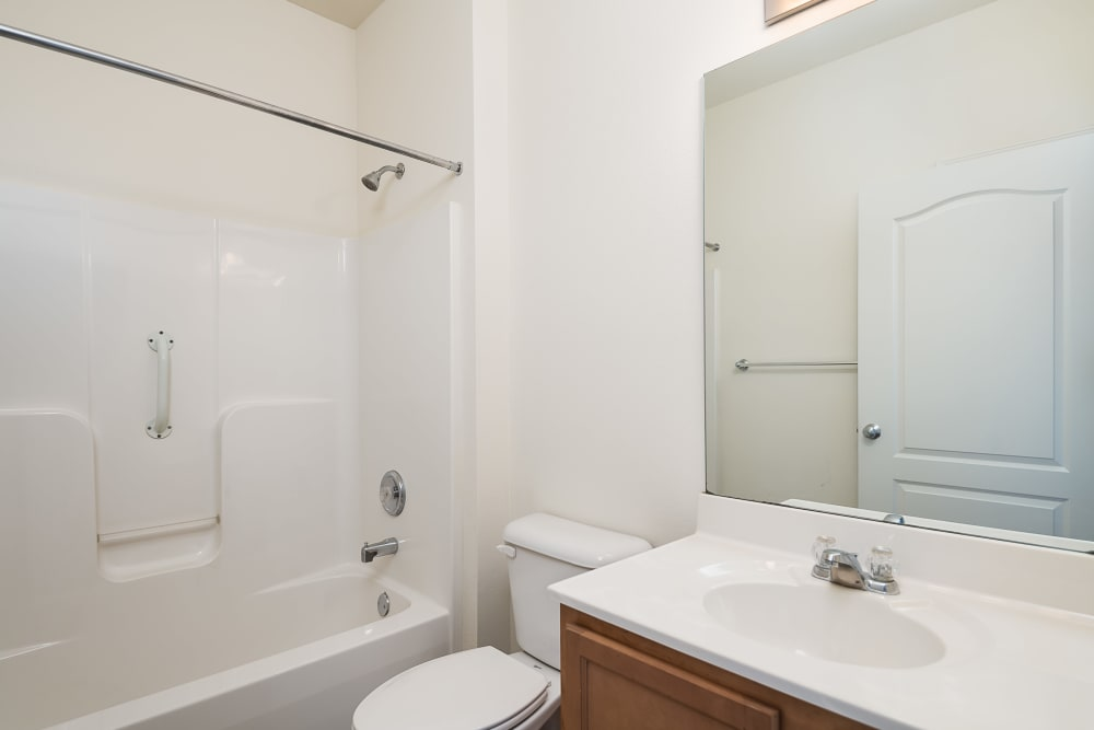 Bright bathroom with a large vanity mirror in an apartment home at Valley Farms in Louisville, Kentucky