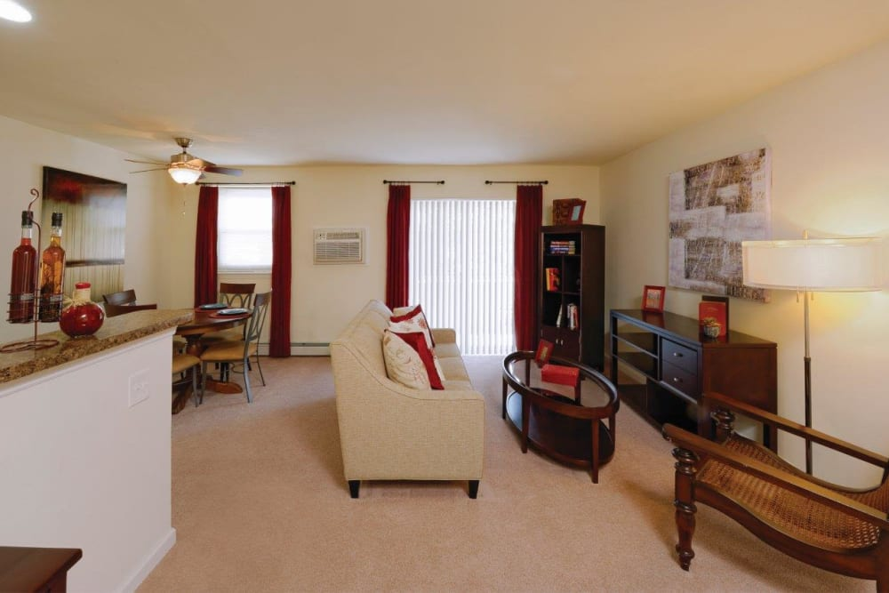 Living room with patio access at Hill Brook Place Apartments in Bensalem, Pennsylvania