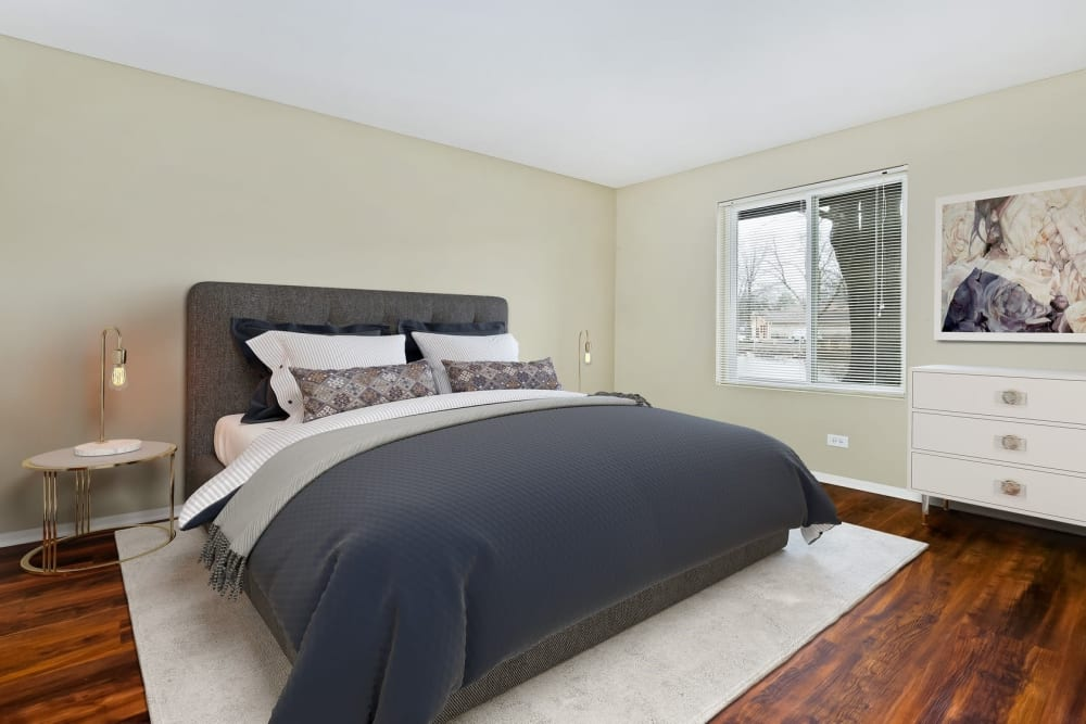 Cozy bedroom with hardwood style flooring at Lakeside Apartments in Lisle, Illinois